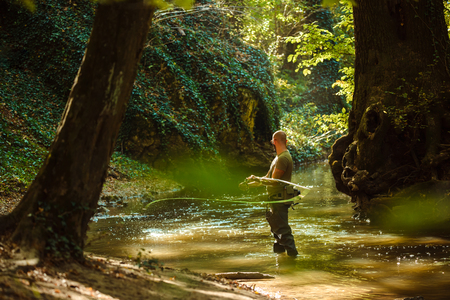 A fisherman fishing with fly fishing in the flowing stream 版權商用圖片