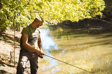Spin fishing on a river with rod