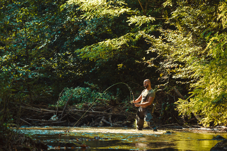 A fisherman fishing with fly fishing in the flowing stream Banque d'images