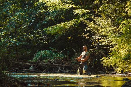 Ein Fischer beim Fliegenfischen im fließenden Bach