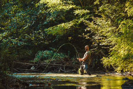 A fisherman fishing with fly fishing in the flowing stream Фото со стока