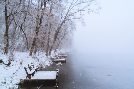 Pier on frozen winter lake in the fog Stock Photo