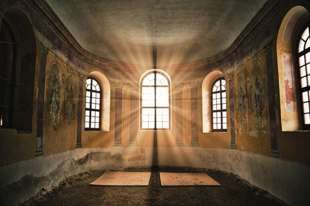 Old deserted church interior with sunlight shining through the window Stock Photo