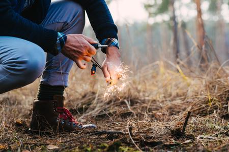 A man makes a fire with a flint Banque d'images