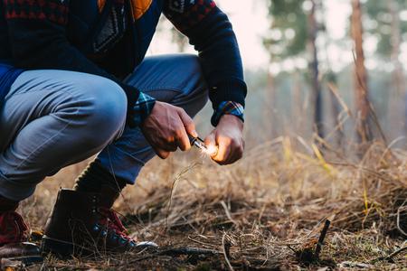 Un homme fait un feu avec un silex