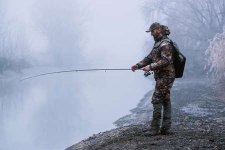 Fisherman fishing with spinning rod on a river bank at misty foggy winter, spin fishing, prey fishing