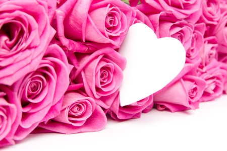 Abstract background made of rose blooms and paper heart photo