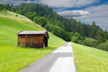 Countryside with road and wooden barn photo