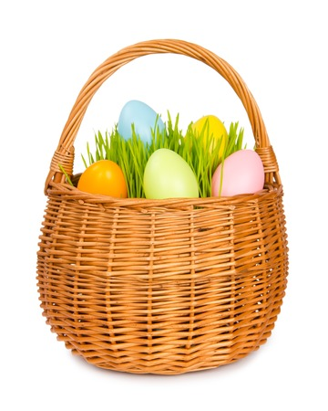 Basket with grass and easter eggs isolated on white photo