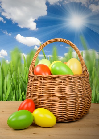 Basket with easter eggs on wooden desk photo