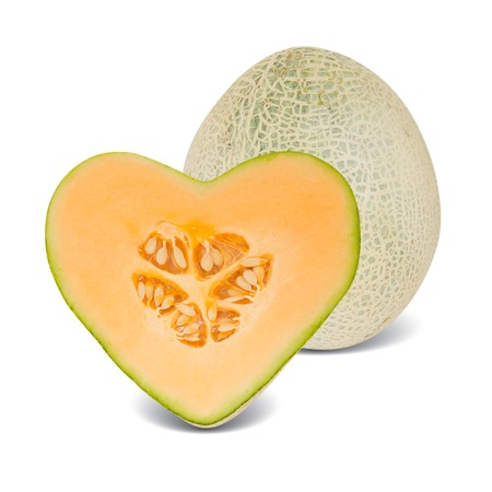 cantaloupe melon with slice in a heart shape isolated on white photo