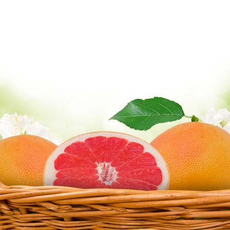 Photo of grapefruit in basket with blossom background photo