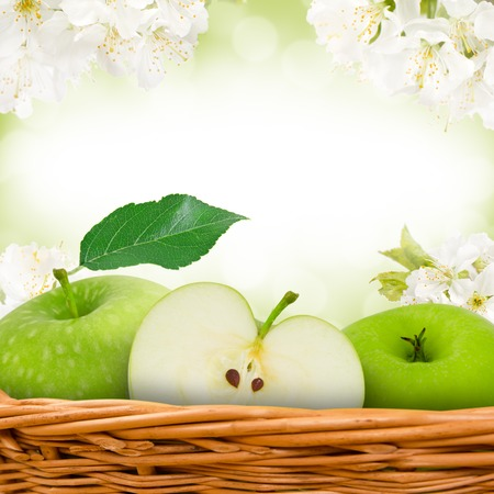 Photo of green apples in basket with apple blossom background photo