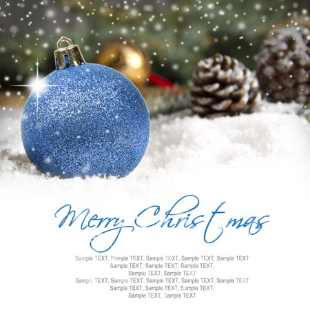 Still life with Christmas ball and cones covered with snow with white space for the text photo