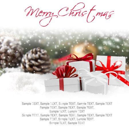 Christmas gifts and cones covered by snow with white space for the text photo