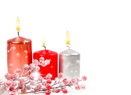 Candles and branch full of red baubles on snow isolated on white photo