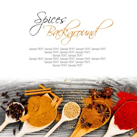 Photo of spoons with spice on wooden board with white space for text photo