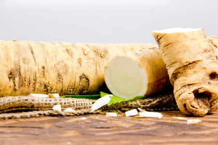 horseradish: horseradish root with slice on burlap and wooden board