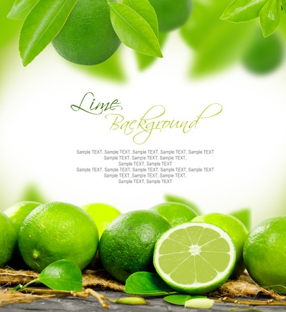 lime green background: lemons with leaves and slice with white space for text Stock Photo