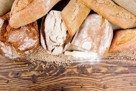 flour: Breads with wheat seeds and flour on burlap and wooden background