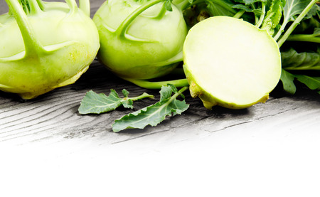 Photo of kohlrabi heads with slice on wooden board with white space Stock Photo