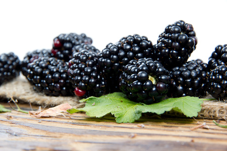 brambleberry: Photo of blackberries with leaves on burlap and wooden board