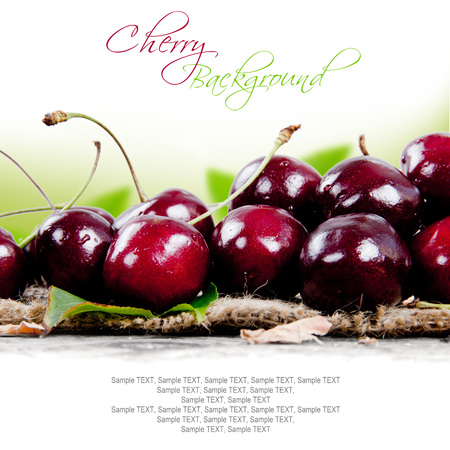 cereza: Photo of cherries with slice and leaves on burlap with white space