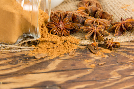 badian: Photo of glass spicebox full of ground star anise spice on burlap and woode board