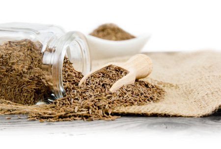 Photo of glass spicebox full of cumin on burlap with white space
