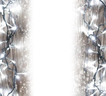 Foto de la tabla de madera iluminada por la cadena ligera de Navidad cubierto de nieve; espacio en blanco para el texto