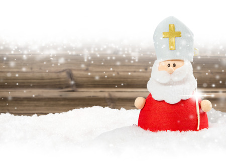 Photo of Saint Nicolas on wooden board background with falling snow and white space Stock Photo