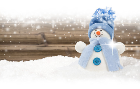 Photo of blue snowman on wooden board background with falling snow and white space