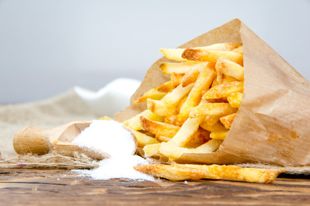 frites: Photo of french fries with salt on wooden surface