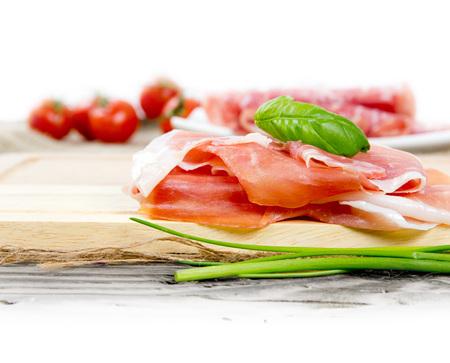 Foto de jamón italiano con hierbas y especias en el tablero de madera