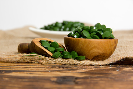 Photo of bowls and spoon full of chlorella pills on burlap with white space