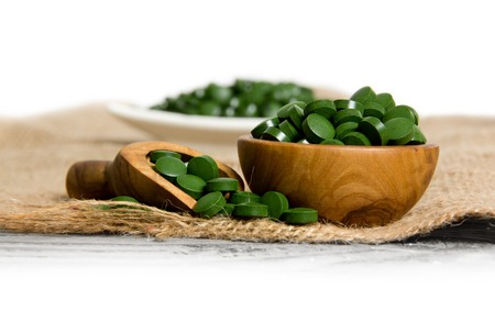 Photo of bowls and spoon full of chlorella pills on burlap with white space Stock Photo - 54652070