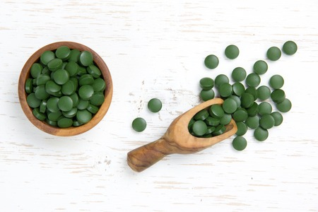 Photo of bowl and spoon full of chlorella pills on white wooden surface Standard-Bild
