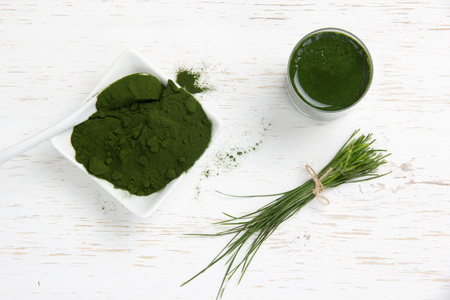 Photo of young barley powder and drink with grass bunch on white wooden surface