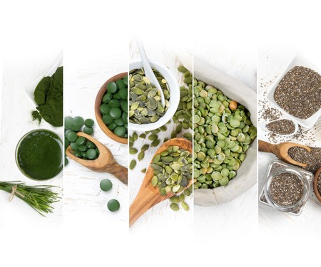 Top view of mixed colorful chlorella and seeds scattered on white wooden surface; dieting and detoxication concept