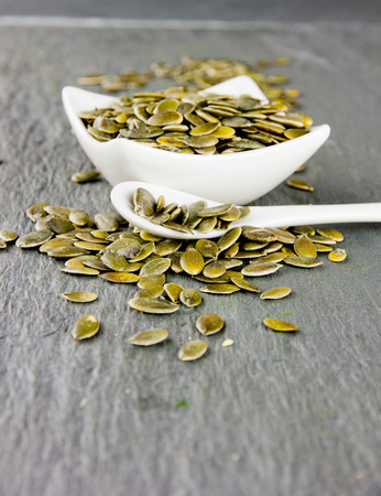 dried gourd: Photo of bowl and spoon full of pumpkin seeds on gray slate surface