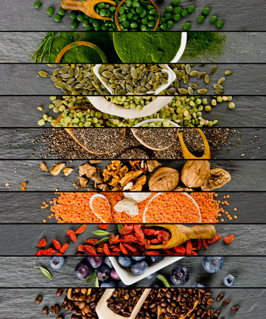 Top view of mixed colorful superfoods scattered on gray slate tile surface Standard-Bild