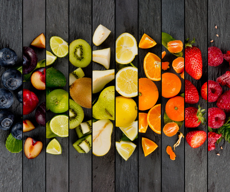 Top view of colorful mix stripes with fruit and slices on gray slate surface; healthy eating concept
