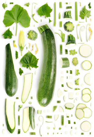 Large collection of green zucchini vegetable pieces, slices and leaves isolated on white background. Top view. Seamless abstract pattern.