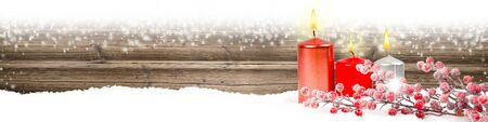 Wide horizontal composition of red candles and bauble branch on wooden background with snowfall. Blank white space for text.