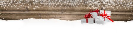 Wide horizontal composition of red ribbon gifts group on wooden background with snowfall. Blank white space for text.