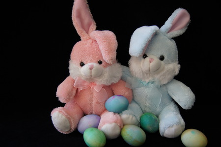 Pink and blue stuffed bunny rabbits with Easter eggs, black background.