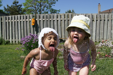 Two little girls with tongues out trying to get a drink from a sprinkler in their bathing suites and hats.
