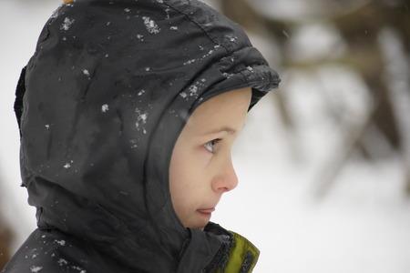 Head shot of boy during snowfall, tongue out. photo