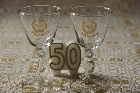 gold table cloth: 50th anniversary glasses and candle, gold and white table cloth background. Stock Photo