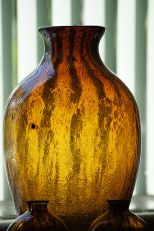 blinds: Sunlit brown and gold jug with green vertical blinds in background. Stock Photo